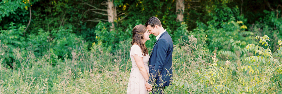 Engagement photos between man and woman in wooded field