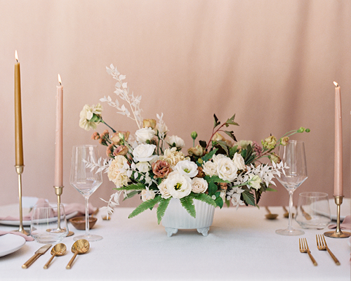 Blush and white dried floral arrangement sitting on wedding reception table