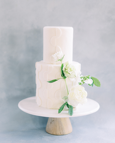 White wedding cake with half circle pattern and small flowers