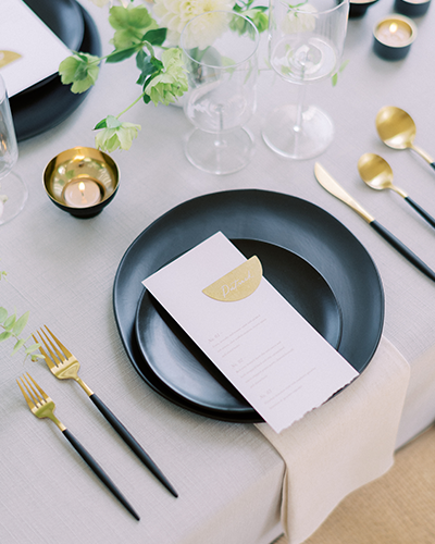 Elegant wedding reception with black plates and accents