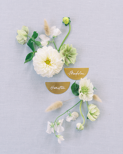 Calligraphed place cards on brass half circles