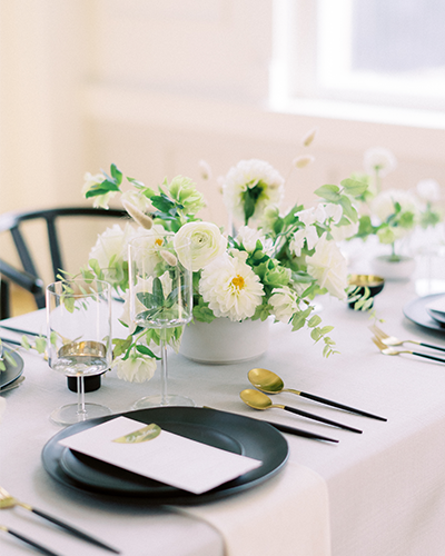 Light blue and black wedding reception table with white floral arrangement