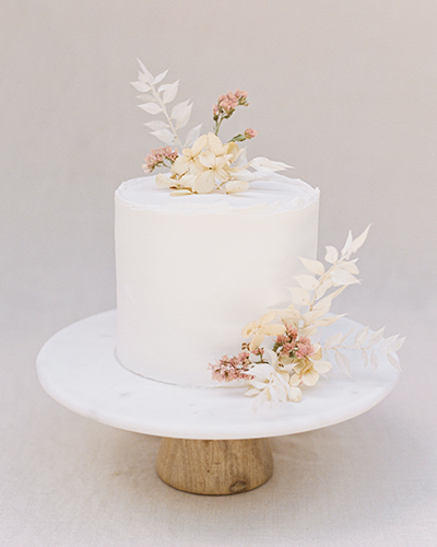 White cake sitting atop marble and wood cake stand