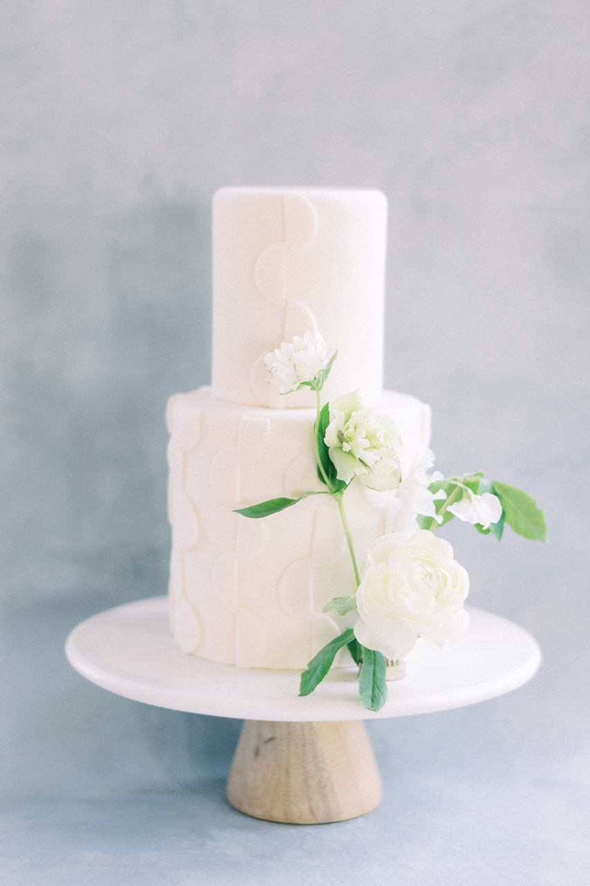 White cake with geometric detailing sitting on marble cake stand