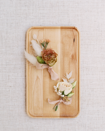 Two wedding boutonnieres sitting on a wooden tray