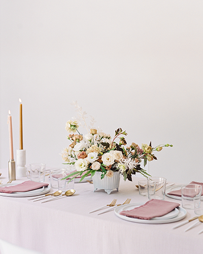 Blush wedding reception table with flowers and tapered candles