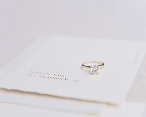 Solitaire diamond engagement ring with white gold band sitting on modern wedding invitation