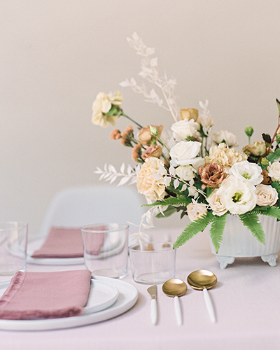 Modern wedding tablescape idea with flowers, blush linen and white plates and flatware
