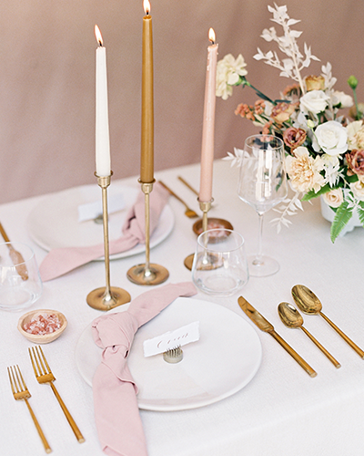 Table setting with plates, gold flatware, flowers and tapered candles in blush and terra cotta