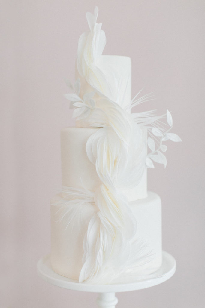 White, three tiered wedding cake with sugar paper detail