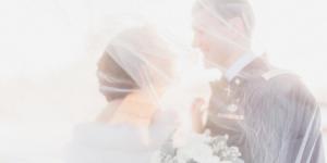 Couple on wedding day underneath a veil