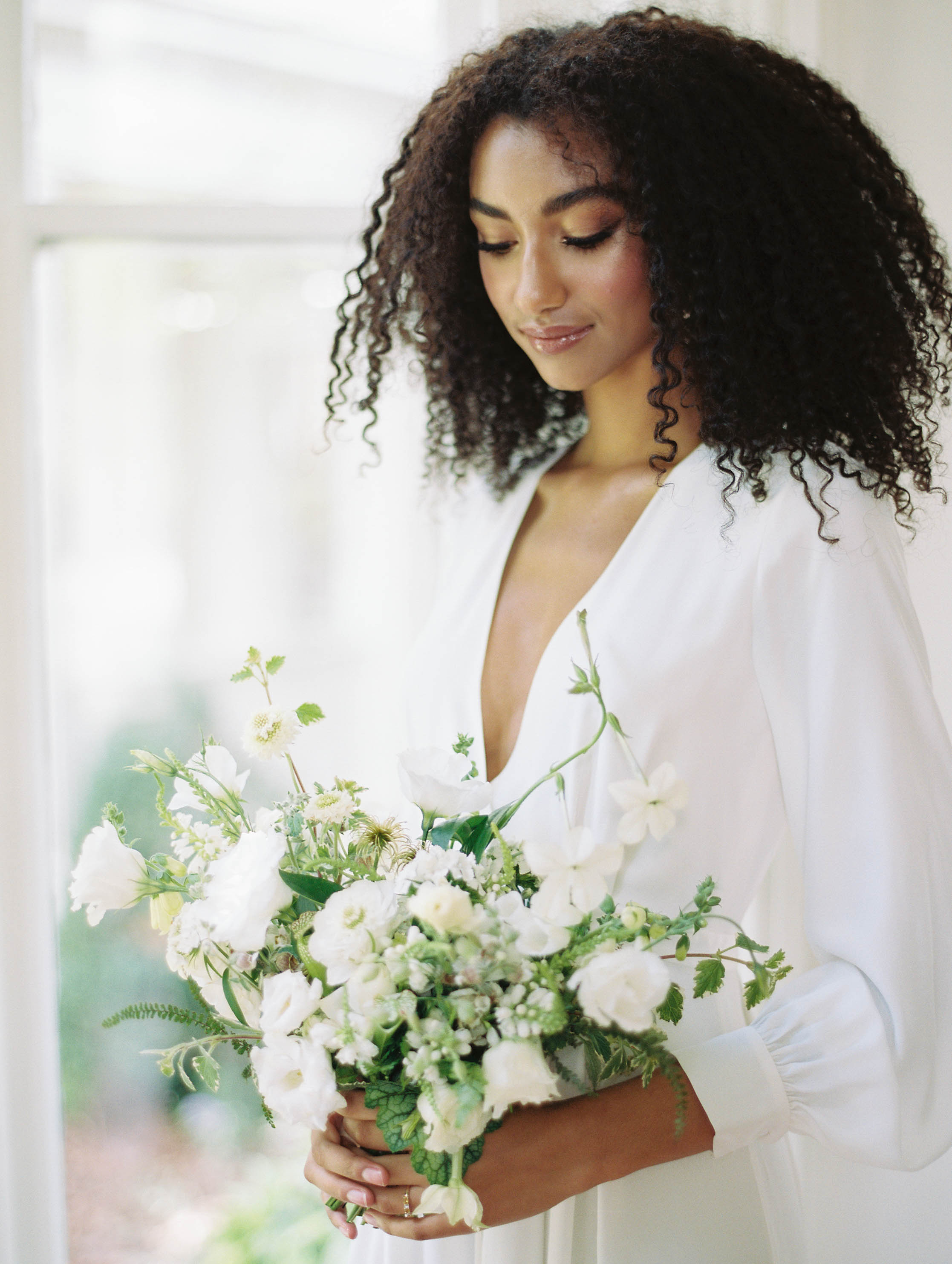 Bride with all white bouquet and long-sleeved wedding gown